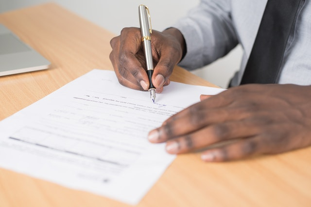 A Hand Signing A Will For What Can Go Wrong When Inheriting A House