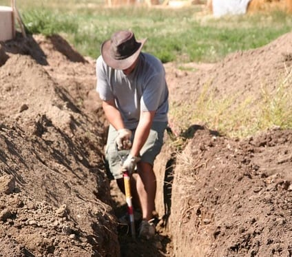 Man Digging A Trench With A Shovel While Standing In The Trench For Post How To Build A Flood Wall